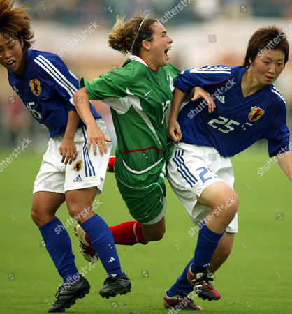 MORA YAMAMOTO YANO Mexico's Iris Adriana Mora, center, is sandwiched by Japan's Emi Yamamoto, right, and Kyoko Yano as they fight for tha ball during the second half of the Women's World Cup preliminary competition play-off match at the National Stadium in Tokyo . Japan defeated Mexico 2-0 to earn the final seat of the World Cup to be held in September in the United States