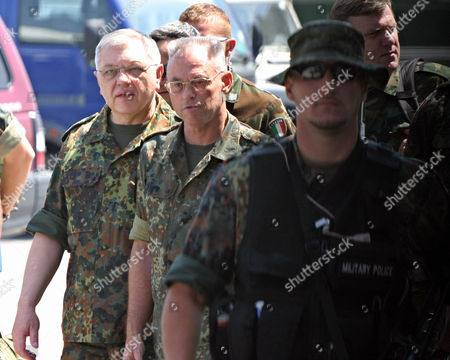 German Gen. Harald Kujat, left, walks behind the commander of the NATO-led peacekeeping force in Kosovo Lt.Gen. Holger Kammerhoff, center, as he wraps up his visit in the Kosovo capital Pristina . Kujat, who led NATO's Military Committee said that the alliance will stay put in Kosovo