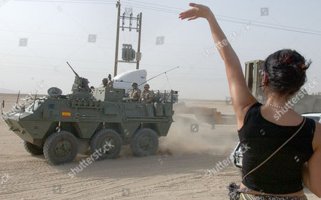 Stock Picture of Spanish reporter Laura Caro, right, from Madrid, waves to Spanish soldiers driving an armoured personnel carrier as they enter Kuwait at Abdaly Border Post, Kuwait, . The last batch of Spanish soldiers withdrawing from Iraq crossed the border from Safwan, Iraq into Kuwait