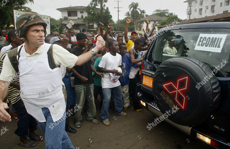 LIBERIA Operations Coordinator for the U.S. Defense Attache Office, Robert Ferguson, clears a path through the jubilant crowd that greeted the convoy containing the ECOWAS (Economic Community of West African States) Mission in Liberia (ECOMIL) team as they visited the U.S. Embassy in the Liberian capital Monrovia