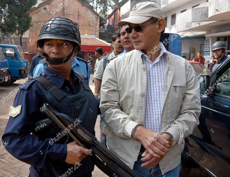 CHARLES SOBHRAJ Confessed serial killer Charles Sobhraj, 59, right, guarded by police officers is taken to the court in Katmandu, Nepal, . Prosecuters charged Sobhraj with murdering two western backpackers in 1975 at a court in Katmandu on Monday