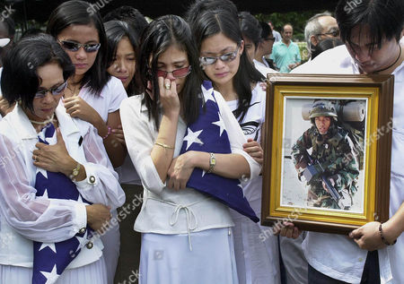 AMELIA NIDA FORTUNE Amelia, wife of Filipino-American US Army Sergeant Maurice Keith Fortune who was killed in action in Ar Ramadi, Iraq, 3rd from right, and mother, Nida, left, grieve with other relatives during full military burial honors inside the former US air base in Clark, Pampanga, northern Philippines on . Fortune, assigned to 2nd Battalion, 17th Field Artillery, 2nd Brigade Combat team, Camp Hovey, Korea, died on Oct. 29, 2004 when an explosive detonated near his vehicle in Iraq