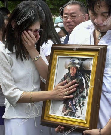 AMELIA FORTUNE Amelia, left, wife of Filipino-American U.S. Army Sgt. Maurice Keith Fortune who was killed in action in Ar Ramadi, Iraq, grieves as she touches the picture of his husband during full military burial honors inside the former U.S. air base in Clark, Pampanga, northern Philippines on . Fortune, assigned to 2nd Battalion, 17th Field Artillery, 2nd Brigade Combat team, Camp Hovey, Korea, died on Oct. 29, 2004 when an explosive detonated near his vehicle in Iraq