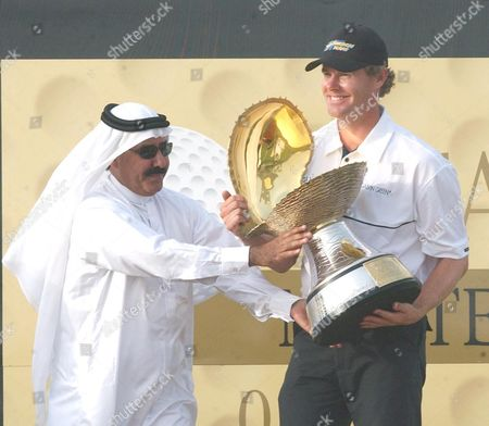 Qatar Masters champion Joakim Haeggman of Sweden, right, receives the Pearl trophy from Qatar Golf Federation President Hassan Al Nuaimy on Sunday at the Doha Golf Club in Doha, Qatar. Haeggman scored an aggregate of 16-under-par 272 for a one stroke victory
