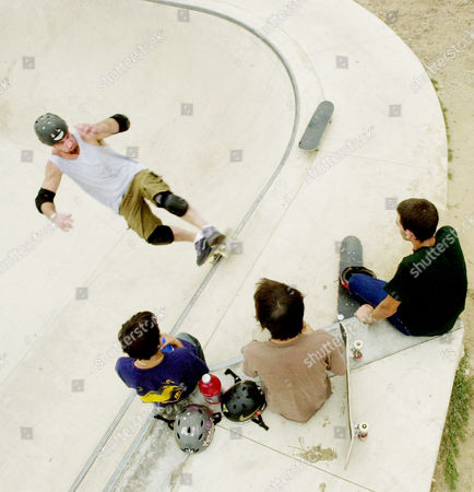 COACCI Joe Boyer, 33, top, of Jackson Township, N.J., skateboards in a bowl, in a skate park at Kennedy Park, in Sayerville, N.J., as fellow skateboarders, from left, John Carson, 12, Danny Macias, 15, and Dane Coacci, 16, watch, . Boyer, who has been skateboarding for 18 years, said when he started there was nothing like the skateparks around, just curbs and illegal locations. The sport once mainly found in the backyard ramps and private skateparks of southern California in the mid-1970s now has a more universal appeal, with more than 1,000 public skateparks open nationwide