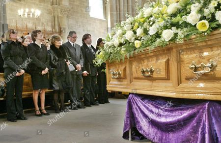 Helene du Lau, center, wife of Sir Peter Ustinov, stands beside other family members and Ustinov's son Igor, right, next to the coffin of late actor, writer and raconteur Sir Peter Ustinov during the funeral ceremony at the Cathedral of St. Pierre in Geneva, Switzerland, . Sir Peter died on Sunday aged 82