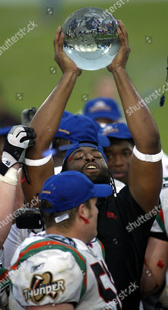 Berlin's Jesse Warren raises the cup after their team won the football world bowl match Duesseldorf Rhine-Fire vs. Berlin Thunder by 26-20 in the western German city of Duesseldorf on