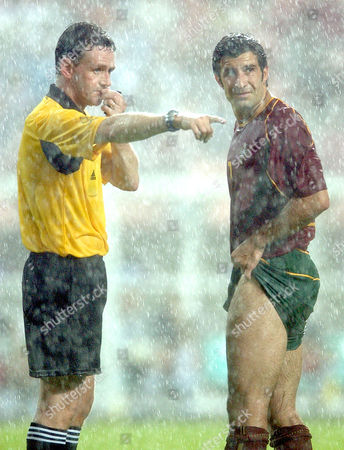 DALLAS FIGO Referee Hugh Dallas of Scotland, left, gestures past Portugal's striker Luis Figo under heavy rain during the 2002 World Cup Group D soccer match between Poland and Portugal at the Jeonju World Cup stadium in Jeonju, South Korea, . The other teams in Group D are South Korea and the United States