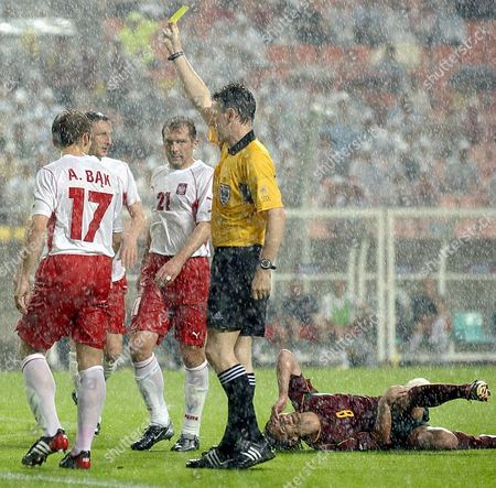 KOZMINSKI Poland's Arkadiusz Bak, left, receives a yellow card from referee Hugh Dallas of Scotland after a foul on Portugal's Joao Pinto, on ground, during their 2002 World Cup Group D soccer match at the Jeonju World Cup stadium in Jeonju, South Korea, . Poland's Marek Kozminski (21) looks on. The other teams in Group D are South Korea and the United States