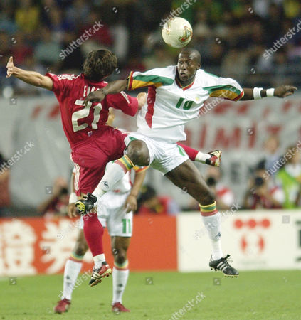 Senegal midfielder Khalilou Fadiga, right, heads the ball away from Turkey midfielder Emre Belozoglu during the 2002 World Cup quarterfinal soccer match between Senegal and Turkey at the Nagai Stadium II in Osaka, Japan