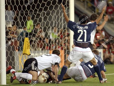 Germany defender Torsten Frings, left, and goalkeeper Oliver Kahn go after a ball, as USA's Landon Donovan holds his arms up during the 2002 World Cup quarterfinal soccer match between Germany and USA, at the Munsu Football stadium in Ulsan, South Korea, . USA players protested referee Hugh Dallas of Scotland the ball was beyond the line
