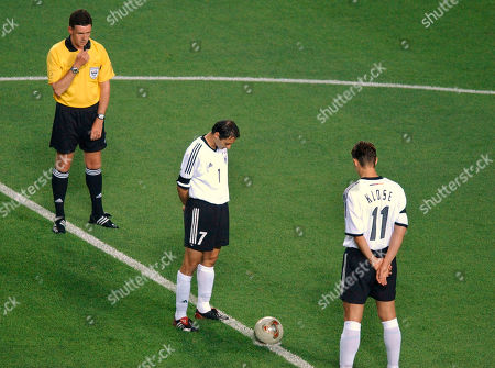German team members Oliver Neuville, center, and Miroslav Klose, right, watched by referee Hugh Dallas stand for one minutes silence before the start of the Germany versus USA 2002 World Cup quarterfinals soccer match at the Munsu Football Stadium in Ulsan, South Korea, . The tribute was for German captain of the World Cup winning 1954 team, Fritz Walter, who died aged 81 on Monday, June 17, 2002