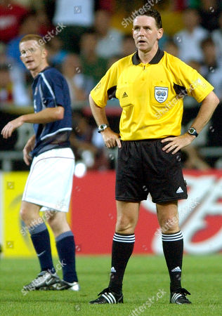 Stock Picture of O'BRIEN DALLAS USA's John O'Brien, background, walks past Scottish referee Hugh Dallas, during the 2002 World Cup quarterfinal soccer match between Germany and USA, at the Munsu Football stadium in Ulsan, South Korea