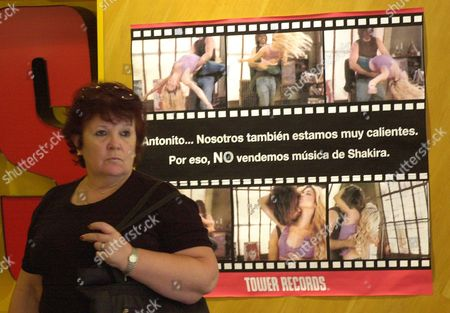 """A woman passes in front of a poster with the sign """"Antonito, we also are very hot. For that reason, we do not sell Shakira's music,"""" at a Tower Records store in Buenos Aires, Argentina, . The statement is accompanied by six video stills that show Antonio de la Rua, son of the former Argentine president and Shakira's boyfriend, dancing with the singer. The boycott reflects negative public sentiment about the video, which many feel is inappropriate in light of Argentina's economic crisis"""