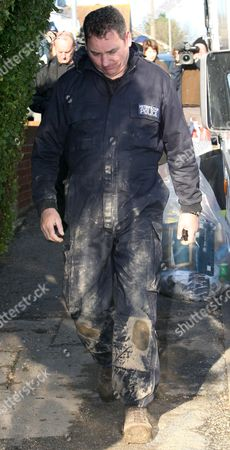 A policeman covered in mud emerges from the house after the second set of remains were discovered. The remains were identified as Vicky Hamilton and Dinah McNicol