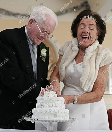James Mason 94 and his wife Peggy 84 cut their wedding cake at the Palace Hotel in Paigton Devon