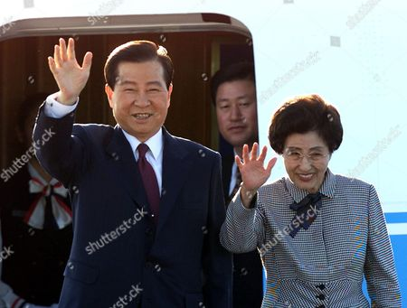 KIM LEE South Korean President Kim Dae-jung, left, and his wife Lee Hee-ho wave from the steps of their plane as they arrive at Shanghai's Pudong airport . Kim will attend the APEC summit in Shanghai, the largest meeting of international leaders ever held in China