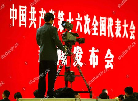 """A Chinese TV camera man films a press conference by Ji Bingxuan, the spokesman for China's 16th Communist Party Congress, in Beijing's Great Hall of the People, . More than 1,300 journalists are registered to cover the week-long congress, which opens Friday. The Chinese characters read """"Chinese Communist Party's 16th National Representative Congress Press Conference"""