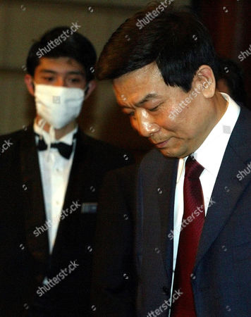 Stock Picture of CHINESE PROPAGANDA CHIEF Cai Fuchao, head of Beijing city's propaganda department, looks down as he finds his seat near a hotel staff wearing a mask during a press conference held in a Beijing hotel on . Chao said inspection teams were being sent to 147 city hospitals to ensure that they were following guidelines on handling potential SARS cases