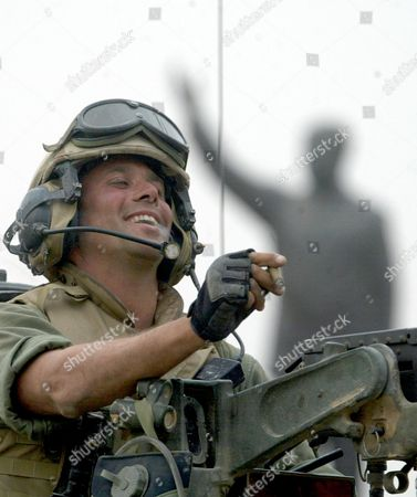 Stock Picture of POPADICH Staff Sgt. Nick Popaditch of the 3rd Battalion, 4th Marines Regiment, smokes a cigar while standing on top of his tank, as he arrives at a main crossroad in downtown Baghdad. A statue of then Iraqi President Saddam Hussein is in the background. On April 7, 2004, while serving as a United States Marine in Iraq, Popaditch's tank was struck by an RPG, with shrapnel carving a path through his sinuses and destroying his right eye. His actions earned him a Silver Star and a Purple Heart but cost him his military career