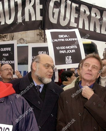 """HUE KOUCHNER French Health Minister Bernard Kouchner, right, and President of the French Communist party Robert Hue, center, partake in a demonstration marking World AIDS Day in Paris . Placards read: """"AIDS : The other war, 10, 000 people dying each day (throughout the world"""