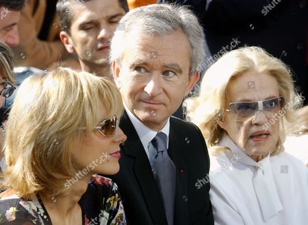ARNAULT MOREAU MERCIER Chief Executive of French luxury goods company LVMH Moet Hennessy Louis Vuitton SA, Bernard Arnault, center, along with his wife Canadian musician Helene Mercier, left, and French actress Jeanne Moreau, attends the presentation of Vuitton's Spring-Summer 2003 ready-to-wear fashion collection, in Paris
