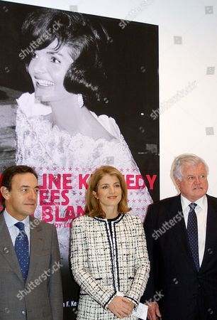 """KENNEDY OWEN-JONES U.S. Senator Edward Kennedy, right, Caroline Kennedy, center, and L'Oreal chairman Lindsay Owen-Jones pose next to the poster for the """"Jacqueline Kennedy - The White House Years"""" exhibition of 70 original outfits worn by Jacqueline Kennedy from 1959 to 1963, at the Fashion and Textile Museum in Paris, . The exhibiton, organized by the John F. Kennedy Library and Museum and the Metropolitan Museum of Art, opens to the public on Nov. 19 and runs to March 16, 2003"""