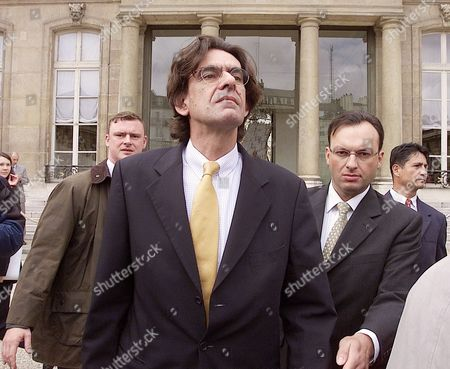 FERRY French Education Minister Luc Ferry, center, leaves the Elysee Palace after the weekly cabinet meeting in Paris, . French government is being confronted with public workers' strikes as it refused to back down from its basic proposal to save the retirement system. Others in photo are unidentified