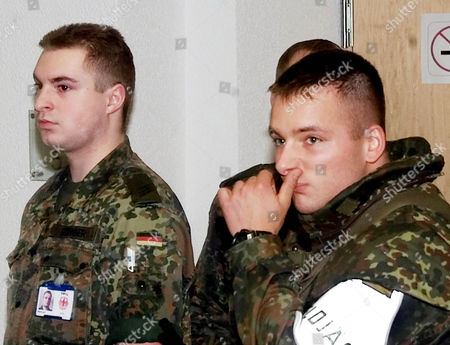 Unidentified German soldiers react as they guard the press conference at the Defense Ministry in Berlin, where the Chief of Staff of the German armed forces, Harald Kujat, announced that two German soldiers died as they removed millitary rocket bombs in Kabul