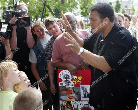 """ALI CHILDREN BINGHAM World famous boxer Muhammad Ali, right, jokes with children as he arrives at a hotel in Riesa, eastern Germany, . Ali is the special guest of a German preview screening of the movie """"Ali"""" in Riesa on Friday, June 28, 2002. Seen in background, center, partly coverd by Ali's hands, is Howard Bingham, a close friend to Ali and co-producer of the movie, who is accompanying Ali on his trip to Riesa"""