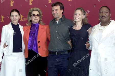 """SAGNIER French director Francois Ozon, center, presents his main actresses Virginie Ledoyen, Catherine Deneuve, Ludivine Sagnier and Firmine Richard, from left to right, during a photo call prior to their press conference about their crime film """" 8 Femmes""""(eight women) during 52nd Berlinale International Film Festival in Berlin Saturday, Feb.9, 2002"""