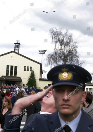 "An unidentified British RAF officer salutes among mourners for the deceased US Cpt. Luke A. Johnson at the 52nd Fighter Wing, Spangdahlem Air Base, western Germany, during a Fly-by ceremony of F-16CJ jets in ""Missing Man"" formation over the base's chapel on . Johnson, a U.S. Air Force F-16 fighter pilot with the 23rd Fighter Squadron, died March 20, 2002, in a crash of his plane while being on routine night maneuvers"