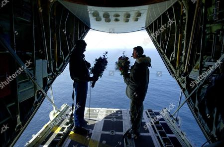 GREBE PHOTOS BY STEPHAN SAVOIA **U. S. Coast Guardsmen Eric Benson, left, and Bryan Grebe, right, hold flower bouquets they tossed off the back of their C-130 Hercules in memory of the sinking of the RMS Titanic, 90 years ago, . Benson and Grebe are part of a 13-member, Coast Guard International Ice Patrol crew surveying the northern shipping lanes of the Atlantic for icebergs