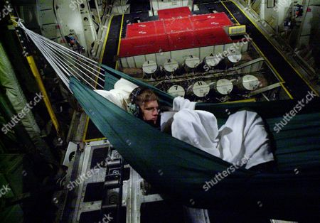 ERIC BENSON PHOTOS BY STEPHAN SAVOIA **U. S. Coast Guard mechanic Eric Benson reads a book while relaxing in a hammock he hung in the cargo area of a C-130 Hercules aircraft during a long mission to plot the movement of icebergs in the Atlantic Ocean . Benson is one of a 13-member Coast Guard International Ice Patrol team flying from the eastern coast of Newfoundland in search of icebergs straying into North Atlantic shipping lanes
