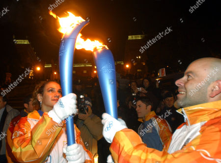 Stock Photo of Olympic torchbearer Elisa Santoni, left, lights her torch with fellow torchbearer Alessandro Arboletto before making her way up the stairs leading to Rome's Campidoglio City Hall with the flame,in the opening stages of the Turin 2006 Winter Olympic Flame tour of Italy, in Rome, .The flame is planned to cover 11,300 kilometers (7,022 miles) throughout Italy involving 10,000 torchbearers, gondolas, a Ferrari sports car and a cavalry regiment before arriving in Turin for the opening ceremony on Feb. 10th