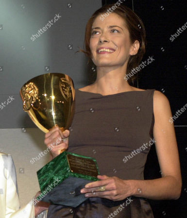 """Italian actress Sandra Ceccarelli holds the Coppa Volpi for best actress at the 58th Venice film festival in the Venice Lido, northern Italy, . Ceccarelli performed in """"Luce dei Miei Occhi"""" (Light of My Eyes) by Italian film director Giuseppe Piccioni. In the background, French actress Jeanne Moreau"""