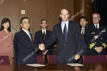 "HATAKEYAMA EVANS CRANCY Morio Hatakeyama, front left, the chief lawyer for the families of the U.S. submarine collision victims, shakes hands with U.S. Navy Capt. Richard Evans after signing a ""reconciliation"" agreement at the U.S. embassy in Tokyo . The families of 33 teachers and students who were aboard the Japanese fishing trawler Ehime-maru that was sunk by the nuclear-powered USS Greenville off Hawaii Feb. 9, 2001 have agreed to a multimillion dollar compensation payout from the U.S. Navy. At right is U.S. Navy Commander Ben Clancy, a signer notary"