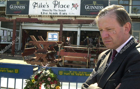 Britain's Ambassador to Israel, Sherard Cowper-Coles pauses at the entrance of Mike's Place bar, a popular nightspot on Tel Aviv's teeming seaside promenade, during a visit to the area, . A suicide bomber, Asif Mohammed Hanif, carrying a British passport, according to the Israeli police, blew himself up at the entrance of the bar, early Wednesday killing himself and three other people