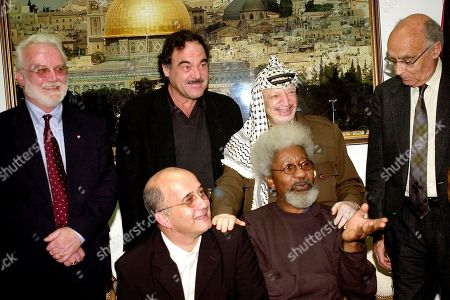 Palestinian leader Yasser Arafat, standing second right, and members of the International Parliament of Writers pose for a photo in his headquarters in the West Bank town of Ramallah . Standing from left to right: Russell Banks, president of the International Parliament of Writers; U.S. film director Oliver Stone; Arafat; and Portugese Nobel literature laureate Jose Saramago. Sitting are French writer Christian Salomon, left, and Nigerian Nobel Prize-winner Wole Soyinka, right