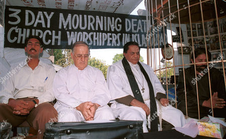 GOOD Christian leader, Julius Salik, sitting in cage to emphasis on Christian-Muslims solidarity, prayes, in Islamabad, Pakistan with, (from left to right), Dilshad Dean, Father John Niven and Father Sardar Good for slain worshippers in church attack. Five people were killed and many injured last Sunday when unidentified attackers hurled grenades in church
