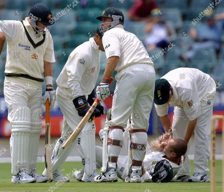 South African fielder Gary Kirsten lies on the ground after being hit above the eye by a shot from Australian batsman Mark Waugh, left, on the first day of the first cricket Test between South Africa and Australia, played at the Wanderers Stadium, Johannesburg, South Africa, . Kirsten left the field for treatment to a cut above the eye