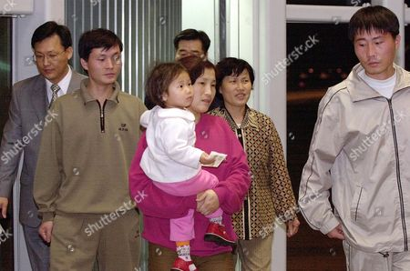 CHUL Airport authorities, background left, guide North Korean asylum seekers, from left: Kim Sung Kook, Kim Han Mi, carried by her Lee Sung Hee, Chung Kyung Sook and Kim Kwang Chul as they arrive at the Incheon International Airport early in Seoul, South Korea. The five landed at the airport, west of Seoul, aboard a Korean Air flight from Manila, Philippines