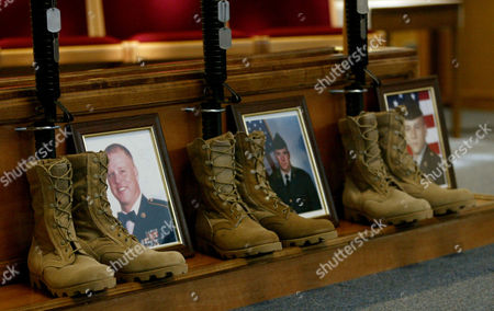 Dog tags, boots, rifles and photos of the fallen soldiers are on display as part of the fallen comrade memorial display at the memorial service for three servicemen from Fort Sill who were killed in the war in Iraq, at Fort Sill, Oklahoma, Thursday, April 10. Pictured in the photographs from left to right are Sgt. 1st Class Randall Rehn, Sgt. Todd Robbins and Spc. Samuel Oaks, Jr. who were killed in Iraq on