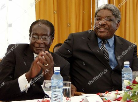 MUGABE Zimbabwean President Robert Mugabe, left, applauds and his Zambian counterpart Levy Mwanawasa smiles during a ceremony honoring former Zambian President Kenneth Kaunda, in Luskaa, Zambia, At the ceremony Mugabe vowed that he would not retire from politics before addressing the critical land issue in Zimbabwe