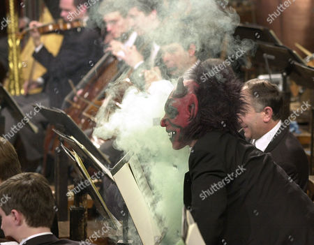 """HARNONCOURT A musician of the Vienna Philharmonic Orchestra masked as a devil appears in a billow of smoke during the Polka """"Luzifer"""" by Johann Strauss, during the traditional New Year's concert at Vienna's Musikverein conducted by Austrian Nikolaus Harnoncourt"""