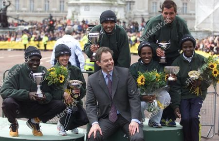 Britain's Prime Minister Tony Blair sits amongst the winners of the London Marathom, Abdelkhader El Mouaziz from Morocco, behind Blair, winner of the Mens London Marathon with the Womens winner Derartu Tulu, from Ethiopia sitting right of Blair, with their cups in London . This is the 21st running of the London Marathon and the cup were presented by the British Prime Minister Tony Blair. Others are from left Paul Tergat from Kenya, second men's marathon, Svetlana Zakharova from Russia second in the womens event, Antonio Pinto 2nd right from Portugal 3rd in Mens and Joyce Dhepchumba at right 3rd in the womens event