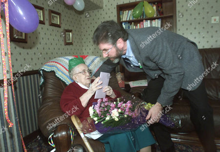 GERRY ADAMS Sinn Fein President Gerry Adams meets Mary Kelly as she celebrates her 100th birthday, during a visit to an old peoples home in the mainly Catholic area of West Belfast, Northern Ireland, . During the visit Adams stated that the Northern Ireland Peace Process cannot withstand any more body blows
