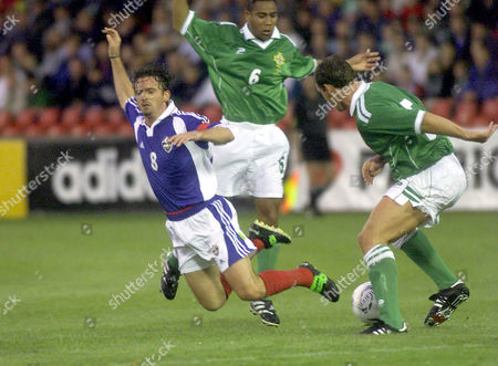 Yugosavia's Predrag Mijatovic takes a fall, left, during a clash with Northern Ireland's Mark Williams and Jeff Witley during their International Challenge Match at Windsor Park in Belfast, Northern Ireland, on