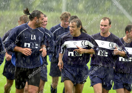 Glasgow Rangers players, German midfielder Christian Nerlinger, right, Italian defender Lorenzo Amoruso, left, and Argentinian striker Claudio Canniggia, center, talk together as they commence pre-season training during heavy rain in Glasgow, Scotland, . Former Agentinian international striker Caniggia agreed to join Rangers at the end of last season