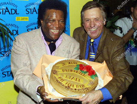 """MOIK BLANCO Austrian entertainer Karl Moik, right, and singer Roberto Blanco pose with a fancy cake during a celebrity party for the 20th jubilee of the tv-show """"Musikanten-Stadl"""" in Munich on"""